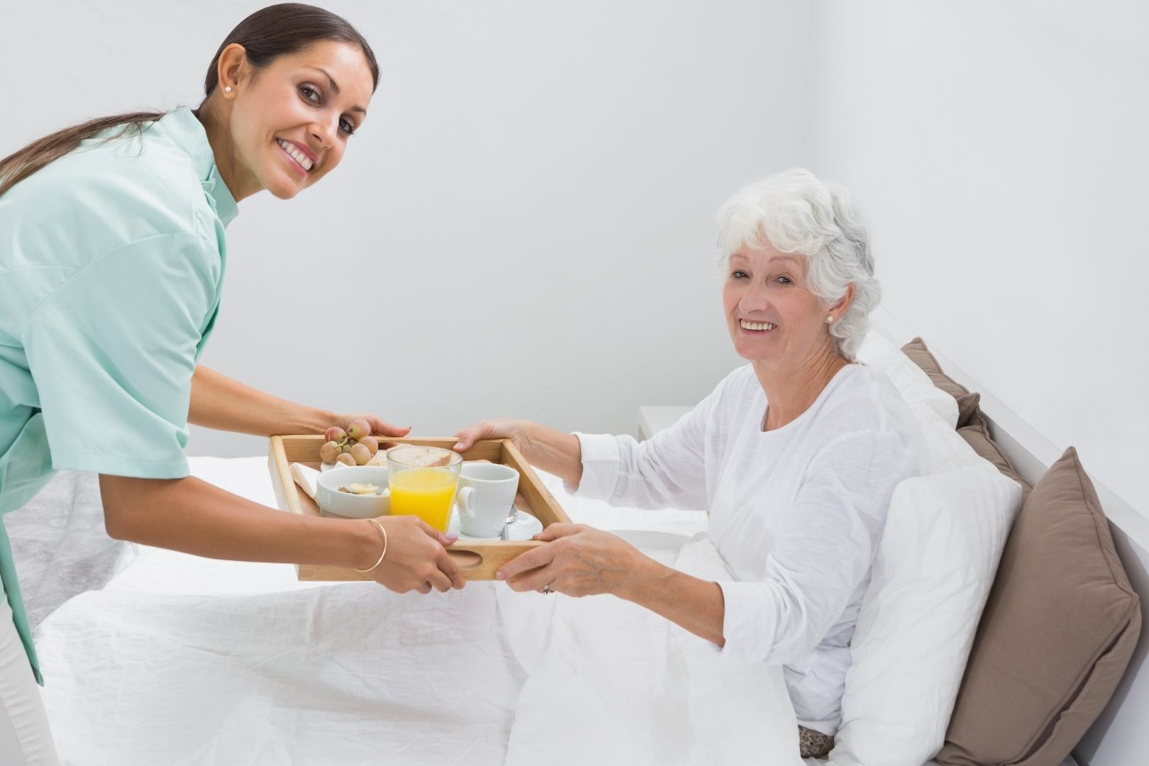 Home nurse giving a breakfast to the old woman on the bed